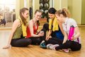 Group of girls in fitness class at the break looking smartphone Stock Photography