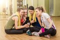 Group of girls in fitness class at the break looking smartphone Royalty Free Stock Photos