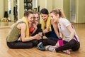 Group of girls in fitness class at the break looking smartphone Stock Image