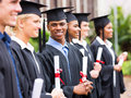 Group of graduates in library happy holding diploma Royalty Free Stock Photo