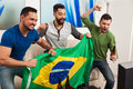 Group of guys cheering for brazil portrait a three male friends while watching tv at home Stock Images