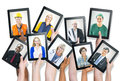 Group of Hands Holding Tablets with People's Faces Royalty Free Stock Photo