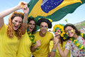 Group of happy brazilian soccer fans commemorating victory with flag in the background Stock Photo