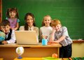 Group of happy classmates with their teacher in class near blackboard Stock Photography