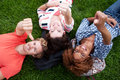 Group of happy college students in grass Royalty Free Stock Image