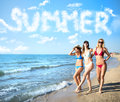 Group of happy friends having fun at ocean beach with summer word made of clouds Royalty Free Stock Photo