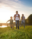 Group of happy friends playing catch-up game and running in summ Royalty Free Stock Photo