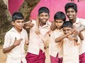 Group of happy funny children friends classmates smiling doing victory peace sign gesture with fingers at the school. School kids Royalty Free Stock Photo