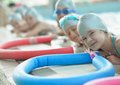 Group of happy kids children at swimming pool class learning to swim Royalty Free Stock Image