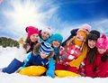 Group of happy kids outside at winter large playing together in snow on sunny day Royalty Free Stock Photo