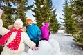 Group of happy kids throw snowballs during fight game together standing behind the snow wall with fir forest on the background Royalty Free Stock Photography
