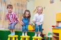 Group of happy preschool kids jumping in kindergarten Stock Images