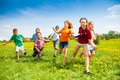 Group of happy running kids large children in the dandelion spring field Royalty Free Stock Image
