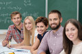 Group of happy successful university students sitting together at a table in the classroom working and studying smiling at the Stock Image