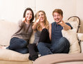 Group of happy teenagers on a sofa pointing attractive at the camera and laughing in merriment one boy and two girls Royalty Free Stock Image