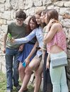 Group of happy young college students taking a photography with mobile phone in the park Royalty Free Stock Images