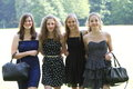 Group of happy young female friends in stylish summer dresses posing arm in arm in a lush green park smiling at the camera Royalty Free Stock Photos