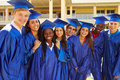 Group of high school students celebrating graduati graduation wearing cape and mortar Royalty Free Stock Images