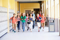 Group of high school students running along corridor towards camera looking happy Royalty Free Stock Image