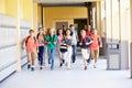 Group of high school students running along corridor towards camera looking happy Royalty Free Stock Image