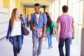 Group of high school students walking along hallway looking at each other smiling Stock Photography