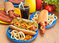 Group of hot dogs on a plate various plastic plates and ingredients with glass coke Royalty Free Stock Images