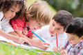 Group of kids coloring outdoors and looking happy Royalty Free Stock Photography
