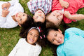 Group of kids happy lying on the floor in a circle Stock Photos