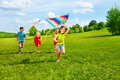 Group of kids with kite four little running in the park happy and smiling Royalty Free Stock Image