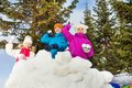Group of kids play snowballs game together standing behind the snow wall fortress with fir forest on the background during winter Stock Images