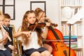 Group of kids playing musical instruments indoors during their concert sitting inside school Royalty Free Stock Photography