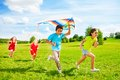 Group of kids run with kite four little boy and girls running in the park on summer day Stock Images