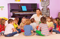 Group of kids sit and listen to teacher tell story Royalty Free Stock Photo