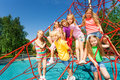 Group of kids sitting together on red ropes smiling boys and girls playground outside in summer Royalty Free Stock Photo