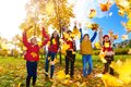 Group of kids throw autumn leaves five boys and girls throwing maple in the park on sunny day Royalty Free Stock Photos