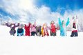 Group of kids throwing snow in the air large diversity looking boys and girls together sitting a row Royalty Free Stock Photography