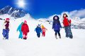 Group of kids walking in snow large bright colorful clothes on plane the mountains Royalty Free Stock Photo