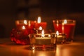 Group of lit candles in the dark assorted glass holders a room with flames Royalty Free Stock Image