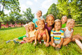 Group of little boys and girls on the lawn large kids diverse looking with nice happy smiles sitting together grass in park Royalty Free Stock Image