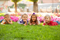 Group of little children relaxing in park a and playing the on the green grass Royalty Free Stock Image