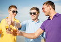 Group of male friends having fun on the beach summer holidays vacation and happy people concept with bottles beer or non alcoholic Stock Image