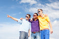 Group of male friends walking on the beach summer holidays vacation happy people concept pointing finger somewhere Royalty Free Stock Photo