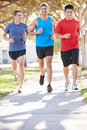 Group of male runners exercising on suburban street running towards camera Stock Photography