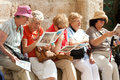 Group of mature female tourists sitting outside the church the holy sepulchre holding brochures Stock Photography