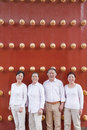 Group of mature people standing next to traditional chinese door portrait Royalty Free Stock Photo