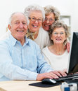 Group of mature people together on computer Stock Image