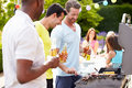 Group of men cooking on barbeque at home in garden chatting to each other Royalty Free Stock Photo