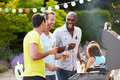 Group of men cooking on barbeque at home holding beer laughing Stock Image