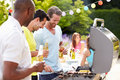 Group of men cooking on barbeque at home holding a bottle beer chatting Royalty Free Stock Images