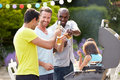 Group of men cooking on barbeque at home making a toast with beer Royalty Free Stock Photo